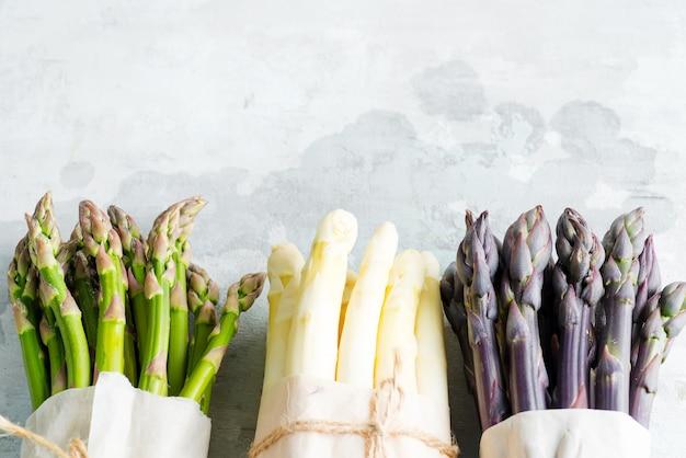 石の壁に新鮮な天然オーガニックアスパラガスの槍から野菜のボーダーフレーム。上面図。