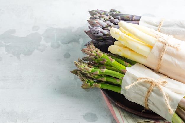 石の壁に新鮮な天然オーガニックアスパラガスの槍から野菜のボーダーフレーム。