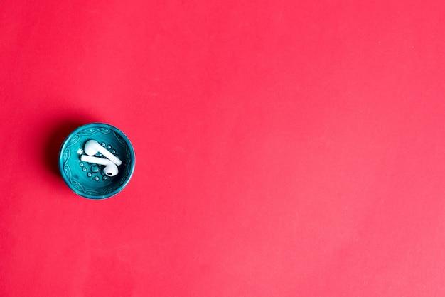 赤い背景の上のワイヤレスイヤホンと小さなセラミックプレート。上面図。現代生活のための日常のアクセサリー。