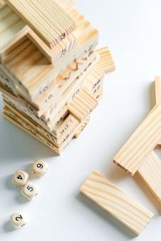Номер один куб на вершине деревянного пирамиды из блоков на светло-серой стене. игра для заработка, развития и обучения.