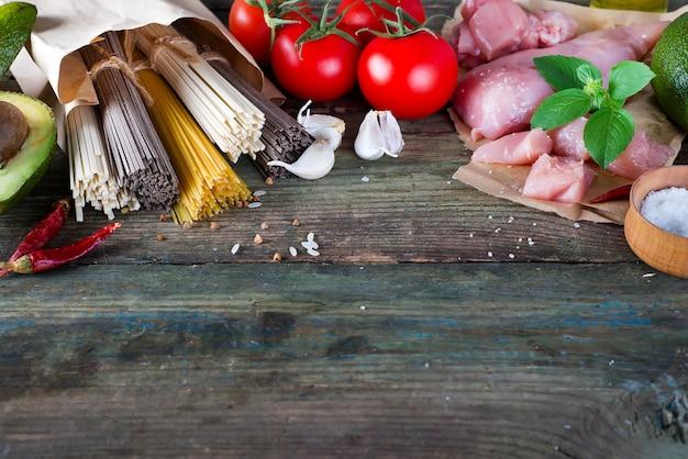 Букет из итальянских спагетти, лапша соба и сомелье, куриное сырое мясо, авокадо с помидорами на старом деревянном