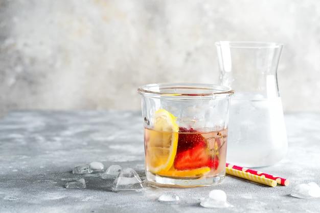 ベリーとレモンフルーツから作られた自家製のさわやかな冷たいレモネード。大理石のグレーのテーブルにアイスキューブとグラスに。