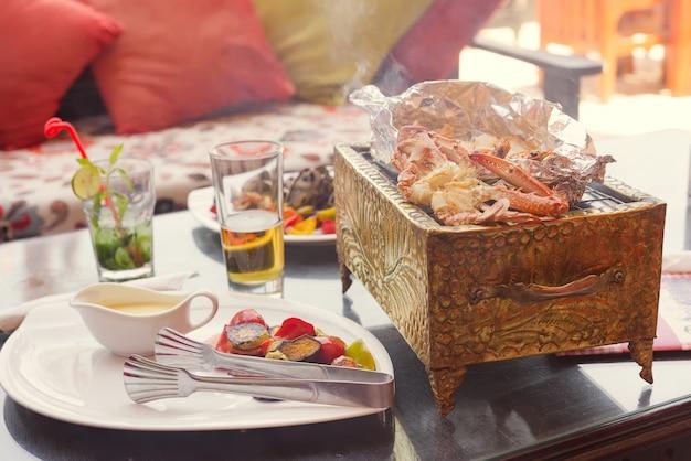 Морепродукты с крабом, кальмарами и креветками на медном гриле с напитком и овощами в кафе