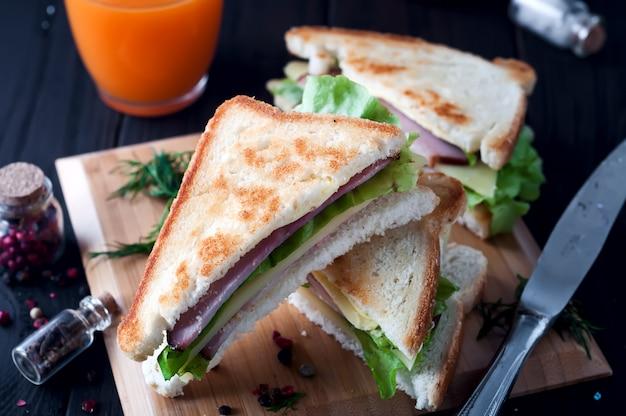 木製の背景にクラブサンドイッチ