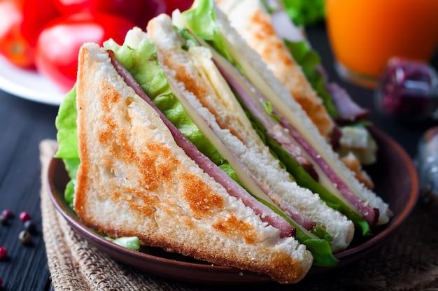 ヘルシーな朝食としてサラダとジュースを使った自家製サンドイッチ