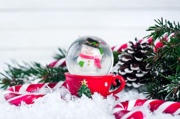 お祝いの背景に雪だるまを持つスノーグローブ