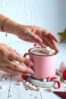 女性の手、ミニマシュマロとキャンディーキャンディーのホットココアのエナメルカップ