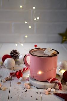 美しいクリスマスのライトが付いているマシュマロとキャンディー・キャンディーのホットココアのエナメルカップ