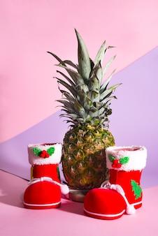 コピースペースのあるデュオトーンの背景にパイナップルを持つクリスマスサンタのブーツ