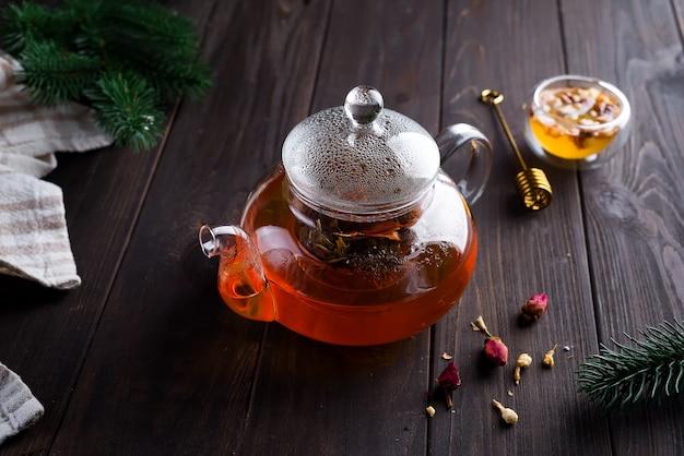 Стеклянный чайник со свежезаваренным травяным чаем и медом на деревянном фоне.
