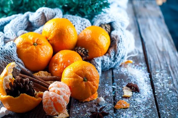 雪で覆われたテーブルの新鮮なタンジェリン