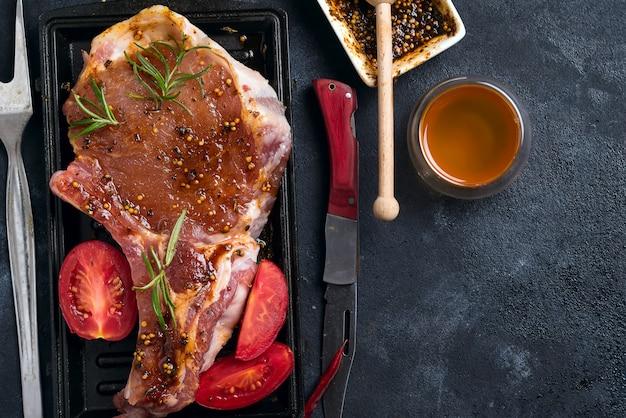 グリルパンにスパイス、ハチミツ、トマトで生のラムチョップをマリネ、クローズアップ
