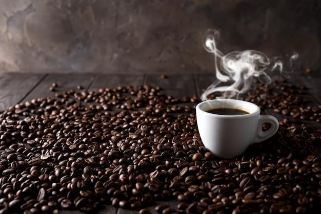 暗い木製の背景にコーヒー穀物の背景に熱いコーヒーのカップ