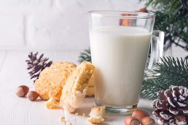 Печенье и молоко для санта-клауса на фоне дерева,