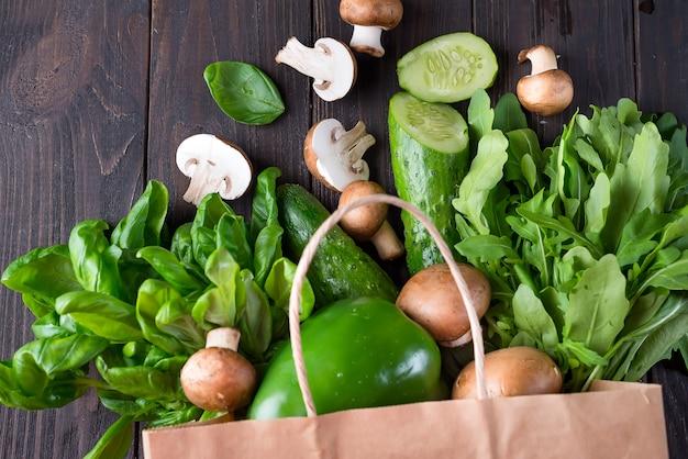 Закройте зеленых овощей на деревянном фоне, плоский лежал