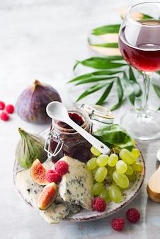 珍味の青いチーズ、フルーツ、白い石のガラスの赤ワインと瓶のジャム