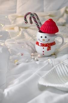 Уютное мягкое одеяло с чашкой в виде снеговика с рождественскими конфетами на кровати