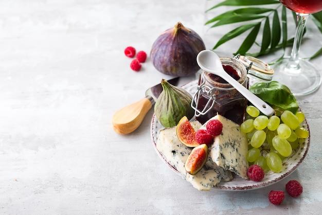 珍味の青いチーズ、果物、白い石の背景にヤシの葉と瓶のジャム、コピースペース