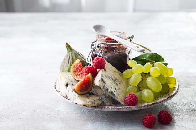 繊細な青いチーズ、白い石の背景に瓶の果物とジャム、コピースペース