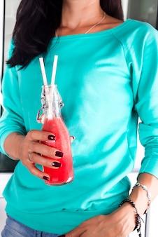 女の子の手の中にスイカスムージーのボトル