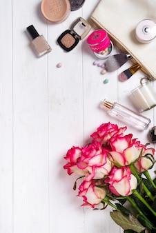 白い木製の背景に女性の化粧品やファッションアイテム