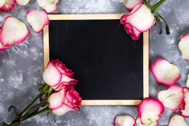 灰色の石のテーブルに美しいバラの花。花の国境。