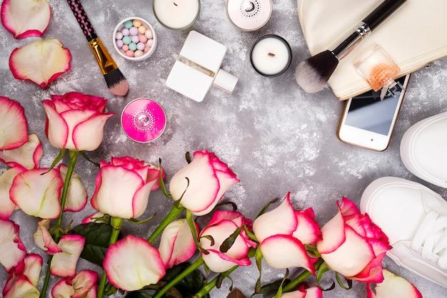 香水、電話、灰色の背景にスニーカーで化粧品とバラの花束