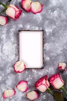 花のフレーム:テキストのコピースペースと石の背景にピンクの白いバラの花束。