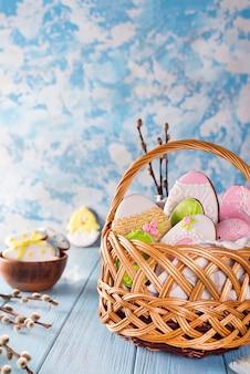 青色の木製の背景に木製のバスケットでイースターのクッキーを装飾