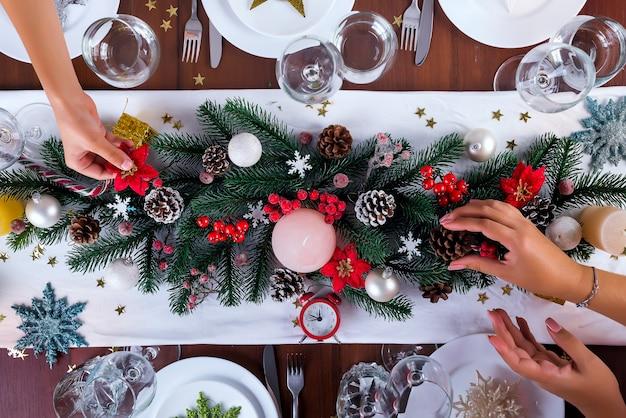 女性と息子は、蝋燭でクリスマスアレンジメントを飾る。