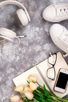 夏休みコンセプト:スマートフォン、白いスニーカー、メモ帳、ヘッドフォン、ペン