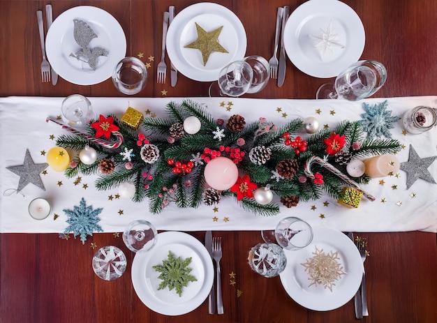 キャンドルでクリスマスアレンジメントを飾る。テーブルウェアのクリスマスデコレーション