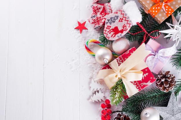 クリスマスの背景にギフトボックス、クリスマスツリー、ミトン、装飾