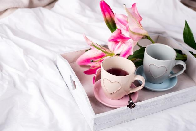 ベッドにホットティーのカップ付きトレー