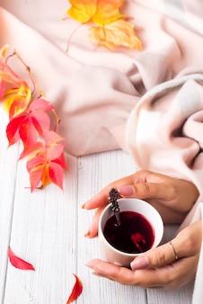 秋の概念。女の手が握るベージュのスカーフで黄色い赤い葉に健康なお茶のカップ