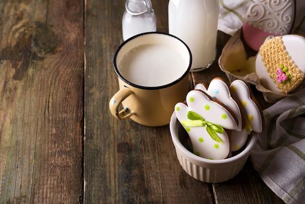 ウサギはイースターのクッキーをミルクで整えます。フォンダンティングで飾られています。