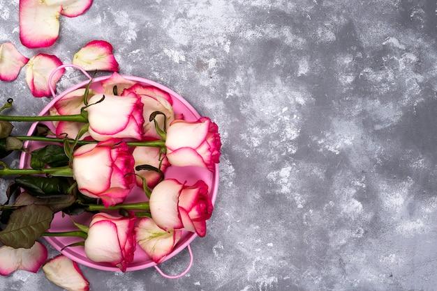 赤い白、石のテーブルにピンクのギフトボックスと花の花束をバラ。