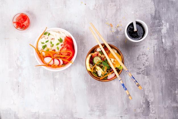Китайский пищевой салат, лапша с овощами и орехами на фоне серого камня