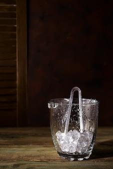 暗い木製の背景、影とコピースペースに氷がいっぱいのシャンパンのバケツ