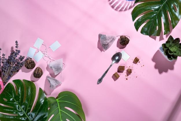 緑の熱帯の葉とティーカップ、ティーバッグ、砂糖、パステルピンクの背景