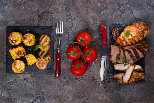 Свежие три вида жареного стейка (курица, свинина, говядина) на шиферной тарелке с травами