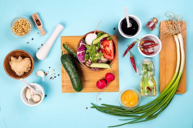 サラダ作り。薄い青色の背景、新鮮なサラダのためのカトラリーとドレッシング成分