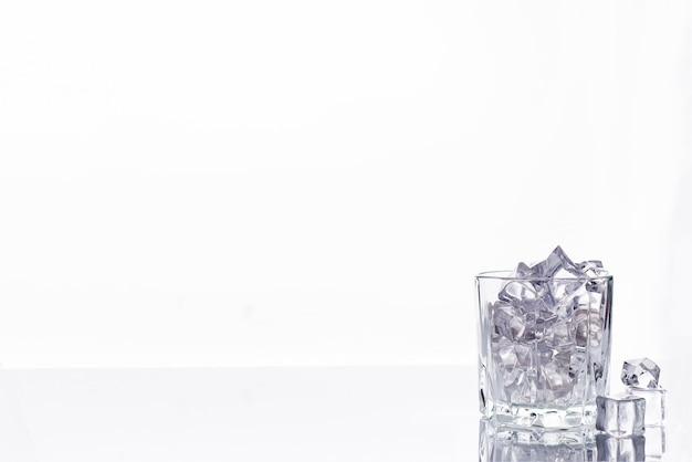 白い背景に氷のキューブと空のガラスの写真