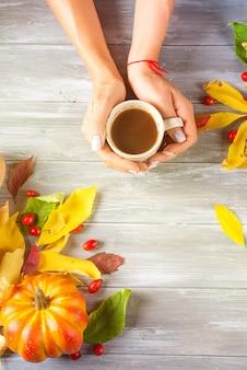 コピースペースと灰色の木製の背景にホットコーヒーを保持する女の子の手。上面図
