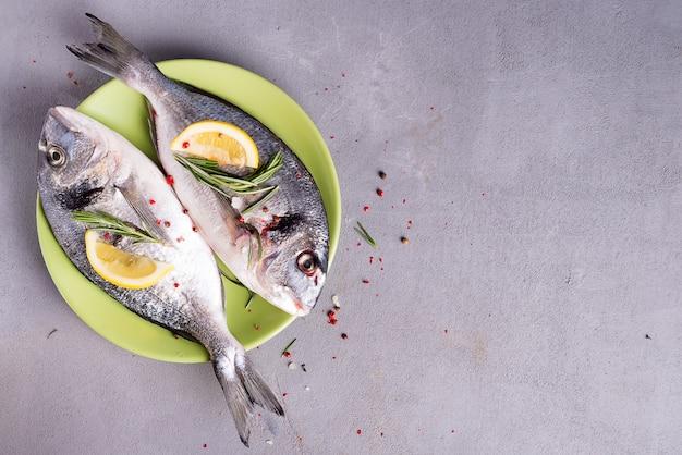 Свежая морская рыба со специями и лимоном, готовая для приготовления на пластине. рыба дорадо или морской лещ