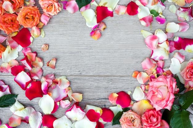 バレンタインの日に木製の背景にバラの花で作られたフレームハート。