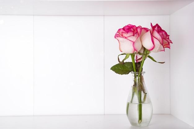 コピースペースを持つ木製の背景の上に花瓶にピンクのバラ