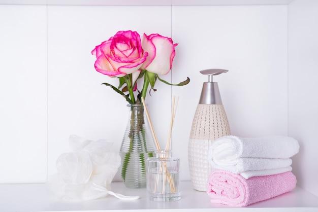 Свежие розы и лепестки роз и различные предметы, используемые в спа-процедурах