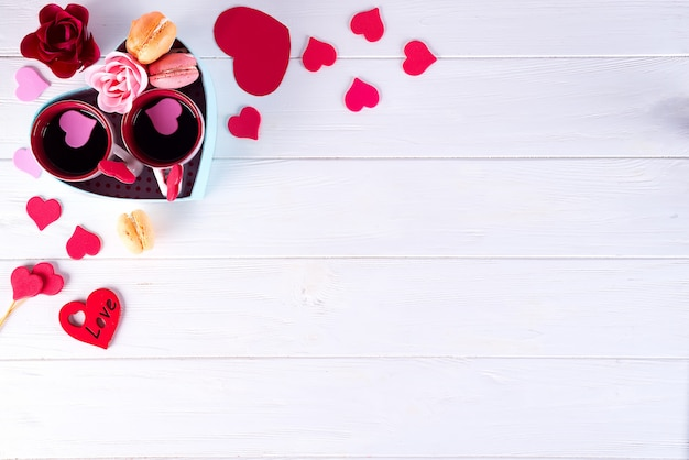 Две чашки кофе, миндальное печенье, цветы в форме коробки сердца на белом фоне.