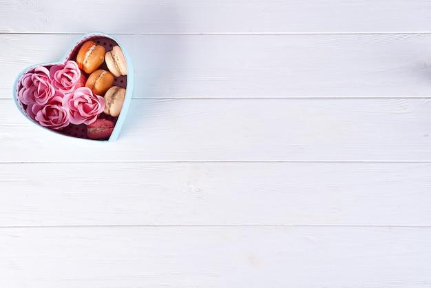 マカロンと白い木製の背景、バレンタインの日にバラのハートボックス